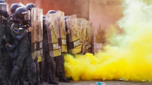 A line of police officers hold riot shields next to a burst of smoky yellow gas.