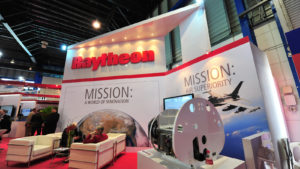 A booth showcasing various technologies offered by Raytheon.