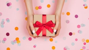 GiftCrowd: two hands holding a gift that is wrapped in brown paper and a red ribbon over a pink background with multicolored confetti