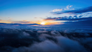 A photograph of the sun setting from a vantage point above the clouds.