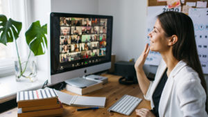 A woman sitting at a desk waves at a large number of people on the videoconferencing software Zoom (ZM stock).