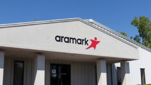 A photo of a building with the Aramark (ARMK) logo on it over the door.