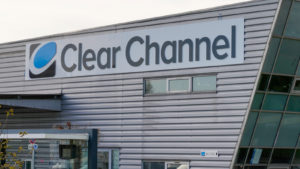 A photograph of a building with the logo for Clear Channel (CCO) on the side.