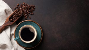 A photo of a cup of coffee and some coffee beans and a towel on a wooden table.