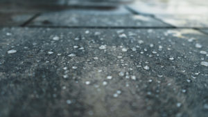 A photograph of rain droplets on a concrete surface.
