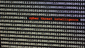 """The words """"cyber threat intelligence"""" are surrounded by a large number of ones and zeroes on a computer display."""