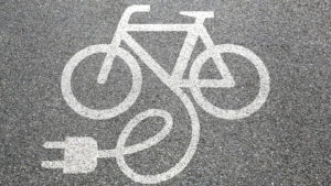 An image of a bike painted in white on asphalt with an electric cord drawn as coming out of the frame.