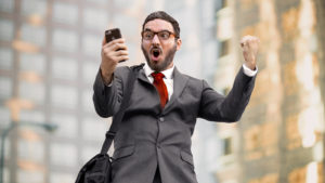 A photograph of an excited man in a suit looking at a cellphone in one hand while raising his other hand in a cheering motion.
