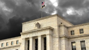 A photo of the entrance of the Federal Reserve Building with dark clouds overhead.