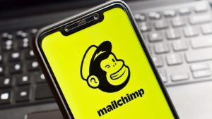 The Mailchimp logo on a smartphone screen with a laptop keyboard in the background.