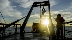 a technician lowering an exploratory robot into the ocean at dawn
