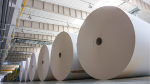 A photo of several large rolls of paper in a warehouse.