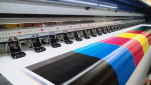 A test page with various bright colors is shown printing from a wide format inkjet printer.