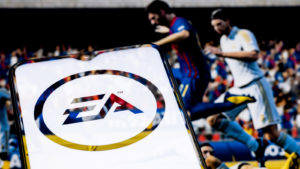 The Electronic Arts (EA stock) logo on a phone in front of a screen displaying EA game from its FIFA franchise