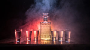 A photo of tequila and glasses on a table against a smoky background.