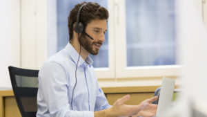A man wearing a headset speaks to someone on a computer.
