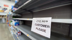 """A photograph of an empty store shelf with a sign reading """"one per customer please."""""""