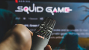 A person holds a TV remote in front of a screen showing the landing page for the Netflix (NFLX) series Squid Game.