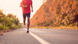 A photograph of a person running along the side of a road.