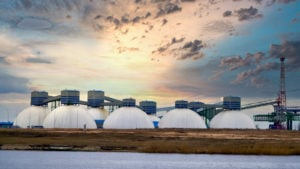 Several natural gas tanks with a sunrise in the background