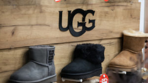 DECK stock: a display of three UGG boots of various colors in a shop with the logo displayed above them
